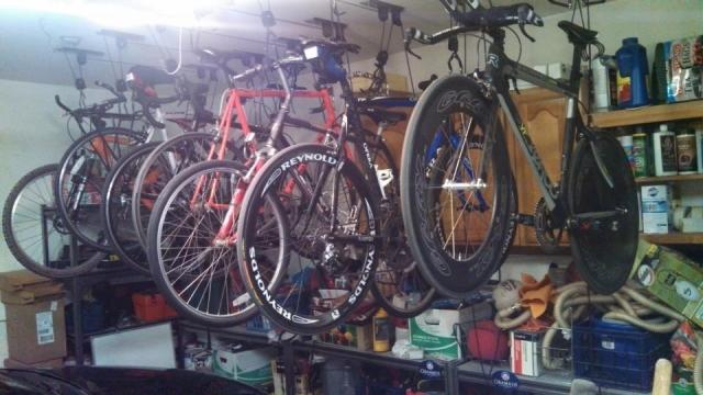 "These are my assortment of bikes in my garage. My two racing bikes with their fancy schmancy carbon wheels are in front - the rest are for ""fun"""